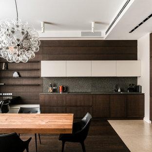 Свежая идея для дизайна: угловая кухня-гостиная в современном стиле с плоскими фасадами, темными деревянными фасадами, черным фартуком, черной техникой, темным паркетным полом и коричневым полом - отличное фото интерьера