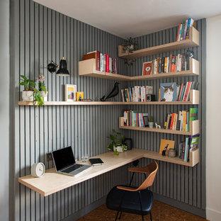 На фото: рабочее место среднего размера в современном стиле с серыми стенами, пробковым полом, встроенным рабочим столом, коричневым полом и панелями на части стены