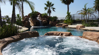 Rock Swimming Pool with Slide, Waterfall and a Table in the pool.