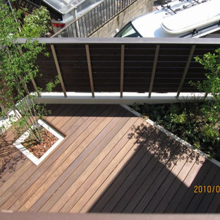 Deck skirting - mid-sized modern courtyard deck skirting idea in Other with an awning