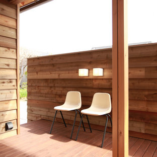 Réalisation d'une terrasse latérale minimaliste avec jupe de finition et une extension de toiture.