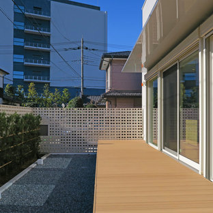 Inspiration for a large modern courtyard deck skirting remodel in Other with an awning