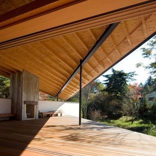 Immagine di un'ampia terrazza etnica con un tetto a sbalzo