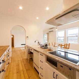他の地域のアジアンスタイルのおしゃれなキッチン (ドロップインシンク、フラットパネル扉のキャビネット、白いキャビネット、御影石カウンター、無垢フローリング、茶色い床) の写真