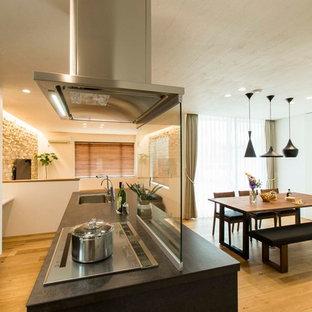 Foto di una cucina parallela etnica con lavello sottopiano, ante lisce, ante nere, parquet chiaro, isola, pavimento beige e top nero