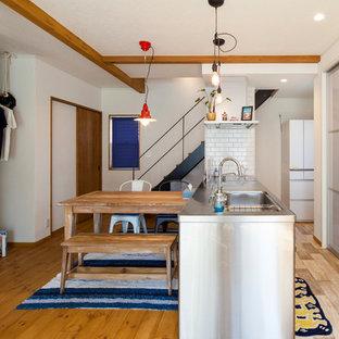 他の地域のII型コンテンポラリースタイルのダイニングキッチンの画像 (無垢フローリング、一体型シンク、ステンレスキャビネット、ステンレスカウンター、白いキッチンパネル、サブウェイタイルのキッチンパネル、ペニンシュラ型、茶色い床)