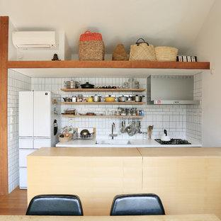 東京23区の小さいアジアンスタイルのおしゃれなキッチン (アンダーカウンターシンク、インセット扉のキャビネット、淡色木目調キャビネット、人工大理石カウンター、白いキッチンパネル、セラミックタイルのキッチンパネル、白い調理設備、合板フローリング、茶色い床、白いキッチンカウンター) の写真