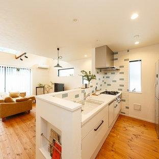 他の地域のモダンスタイルのおしゃれなキッチン (一体型シンク、フラットパネル扉のキャビネット、白いキャビネット、無垢フローリング、茶色い床、白いキッチンカウンター) の写真