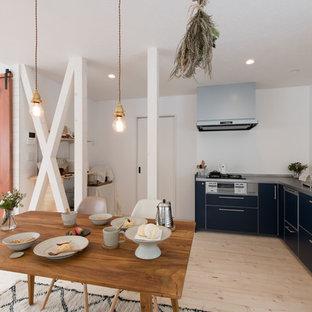 札幌のカントリー風おしゃれなキッチン (シングルシンク、フラットパネル扉のキャビネット、青いキャビネット、ステンレスカウンター、白いキッチンパネル、淡色無垢フローリング、ベージュの床) の写真