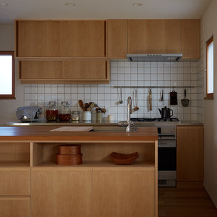 Photo of a mid-sized asian galley open plan kitchen in Other with an undermount sink, flat-panel cabinets, light wood cabinets, wood benchtops, white splashback, porcelain splashback, panelled appliances, medium hardwood floors, multiple islands, brown floor and beige benchtop.