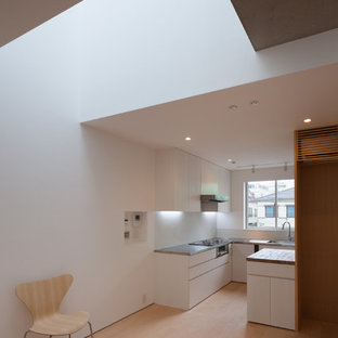 Modern enclosed kitchen in Tokyo with a submerged sink, flat-panel cabinets, white cabinets, stainless steel worktops, white splashback, stainless steel appliances, plywood flooring, an island and beige floors.
