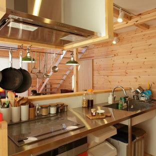 他の地域のカントリー風おしゃれなキッチン (シングルシンク、ステンレスカウンター、白いキッチンパネル、淡色無垢フローリング、茶色い床) の写真