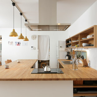 Imagen de cocina en U, asiática, con fregadero de un seno, salpicadero blanco, suelo de madera clara y suelo marrón