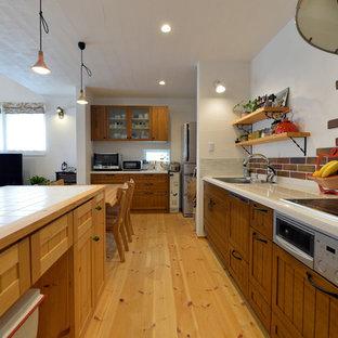 他の地域の中サイズのアジアンスタイルのおしゃれなキッチン (シングルシンク、落し込みパネル扉のキャビネット、濃色木目調キャビネット、タイルカウンター、無垢フローリング、茶色い床) の写真