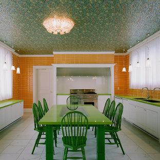 東京23区のL型ヴィクトリアン調のダイニングキッチンの画像 (ダブルシンク、レイズドパネル扉のキャビネット、白いキャビネット、オレンジのキッチンパネル、サブウェイタイルのキッチンパネル、シルバーの調理設備)