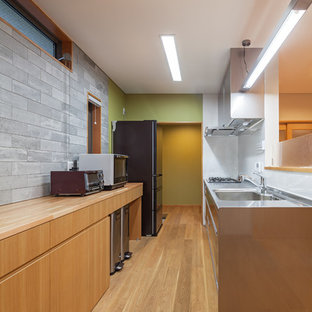 Exemple d'une cuisine linéaire asiatique avec un évier 1 bac, un placard à porte plane, des portes de placard en bois brun, un plan de travail en inox, un sol en bois brun, une péninsule et un sol marron.