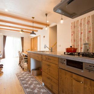 他の地域のラスティックスタイルのおしゃれなキッチン (シングルシンク、濃色木目調キャビネット、淡色無垢フローリング、アイランドなし、フラットパネル扉のキャビネット、茶色い床) の写真