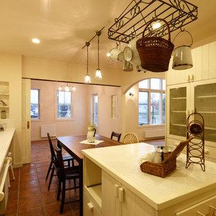 他の地域のシャビーシック調のおしゃれなキッチン (テラコッタタイルの床、茶色い床) の写真