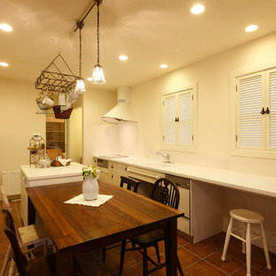 他の地域のシャビーシック調のおしゃれなキッチン (一体型シンク、フラットパネル扉のキャビネット、ベージュのキャビネット、テラコッタタイルの床、茶色い床、白いキッチンカウンター) の写真