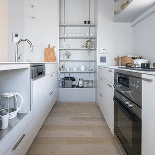 東京23区の北欧スタイルのおしゃれなキッチン (アンダーカウンターシンク、インセット扉のキャビネット、白いキャビネット、白いキッチンパネル、シルバーの調理設備、淡色無垢フローリング、ベージュの床、白いキッチンカウンター) の写真