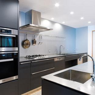 他の地域の広いコンテンポラリースタイルのおしゃれなアイランドキッチン (一体型シンク、フラットパネル扉のキャビネット、黒いキャビネット、ステンレスカウンター、淡色無垢フローリング、ベージュの床) の写真