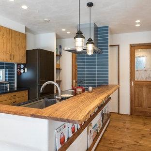 名古屋のエクレクティックスタイルのおしゃれなキッチン (濃色木目調キャビネット、濃色無垢フローリング、茶色い床、アンダーカウンターシンク、フラットパネル扉のキャビネット、青いキッチンパネル、サブウェイタイルのキッチンパネル、黒いキッチンカウンター) の写真