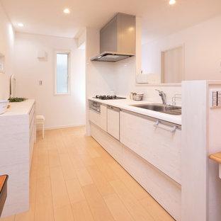 他の地域のカントリー風おしゃれなキッチン (人工大理石カウンター、白いキッチンパネル、黒い調理設備、塗装フローリング、白いキッチンカウンター) の写真