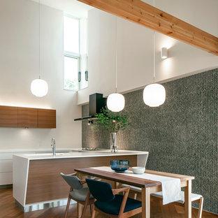 他の地域のコンテンポラリースタイルのおしゃれなキッチン (フラットパネル扉のキャビネット、白いキャビネット、無垢フローリング、茶色い床、白いキッチンカウンター) の写真