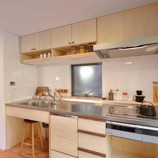 他の地域のアジアンスタイルのおしゃれなキッチン (一体型シンク、フラットパネル扉のキャビネット、淡色木目調キャビネット、ステンレスカウンター、白いキッチンパネル、淡色無垢フローリング、茶色い床、ベージュのキッチンカウンター) の写真