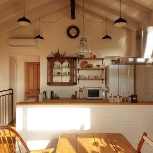 東京都下の北欧スタイルのおしゃれなキッチン (木材カウンター、白いキッチンパネル、サブウェイタイルのキッチンパネル、白い調理設備、無垢フローリング、茶色い床、茶色いキッチンカウンター) の写真