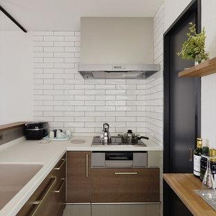 小さいインダストリアルスタイルのおしゃれなペニンシュラキッチン (一体型シンク、フラットパネル扉のキャビネット、中間色木目調キャビネット、グレーのキッチンパネル、茶色い床、茶色いキッチンカウンター) の写真