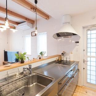 他の地域, のカントリー風おしゃれなキッチン (シングルシンク、フラットパネル扉のキャビネット、ステンレスキャビネット、ステンレスカウンター、白いキッチンパネル、淡色無垢フローリング、茶色い床) の写真