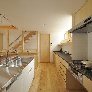 他の地域の北欧スタイルのおしゃれなキッチン (一体型シンク、フラットパネル扉のキャビネット、ステンレスカウンター、無垢フローリング、茶色い床、黒いキッチンカウンター) の写真