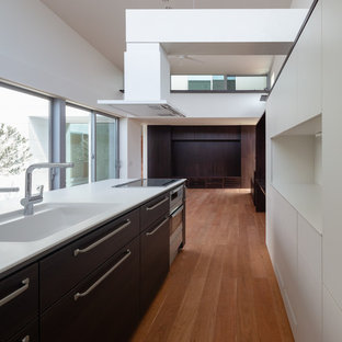 This is an example of a modern single-wall open plan kitchen in Other with an integrated sink, flat-panel cabinets, dark wood cabinets, composite countertops, stainless steel appliances, plywood flooring, an island, brown floors and white worktops.