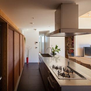 横浜の中サイズのコンテンポラリースタイルのおしゃれなキッチン (一体型シンク、フラットパネル扉のキャビネット、ステンレスキャビネット、ステンレスカウンター、シルバーの調理設備の、セラミックタイルの床、黒い床) の写真