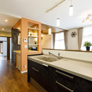 Asian single-wall open plan kitchen in Other with an undermount sink, flat-panel cabinets, brown cabinets, solid surface benchtops, white splashback, slate splashback, plywood floors, a peninsula, brown floor and beige benchtop.