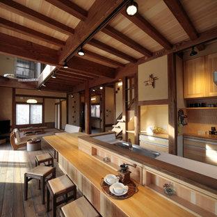 他の地域のアジアンスタイルのおしゃれなキッチン (アンダーカウンターシンク、フラットパネル扉のキャビネット、中間色木目調キャビネット、ベージュキッチンパネル、シルバーの調理設備、濃色無垢フローリング、茶色い床、白いキッチンカウンター、表し梁、板張り天井) の写真