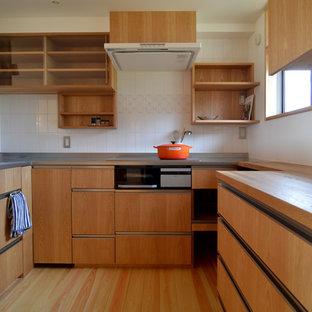 他の地域の中サイズのおしゃれなキッチン (シングルシンク、フラットパネル扉のキャビネット、中間色木目調キャビネット、ステンレスカウンター、茶色いキッチンパネル、木材のキッチンパネル、シルバーの調理設備の、淡色無垢フローリング、アイランドなし、茶色い床、茶色いキッチンカウンター) の写真