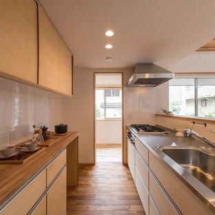 東京23区のアジアンスタイルのおしゃれなキッチン (シングルシンク、フラットパネル扉のキャビネット、淡色木目調キャビネット、ステンレスカウンター、白いキッチンパネル、無垢フローリング、茶色い床、茶色いキッチンカウンター) の写真