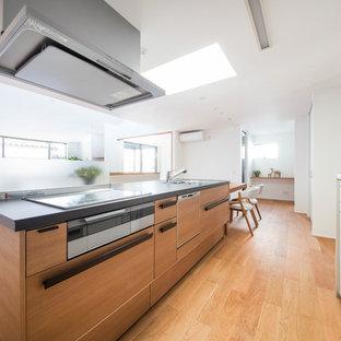 Idée de décoration pour une cuisine américaine linéaire minimaliste avec un évier encastré, un placard à porte plane, des portes de placard en bois brun, un électroménager en acier inoxydable, un sol en contreplaqué, un îlot central, un sol marron et un plan de travail noir.