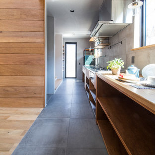 Photo of an industrial single-wall open plan kitchen in Other with an integrated sink, open cabinets, medium wood cabinets, stainless steel benchtops, porcelain splashback, stainless steel appliances, porcelain floors, grey splashback and grey floor.