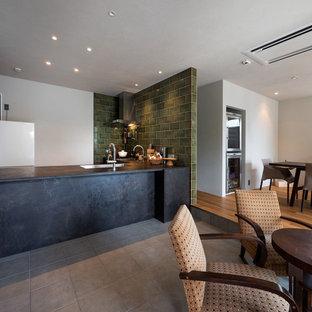 アジアンスタイルのおしゃれなキッチン (アンダーカウンターシンク、インセット扉のキャビネット、ヴィンテージ仕上げキャビネット、緑のキッチンパネル、シルバーの調理設備の、グレーの床) の写真