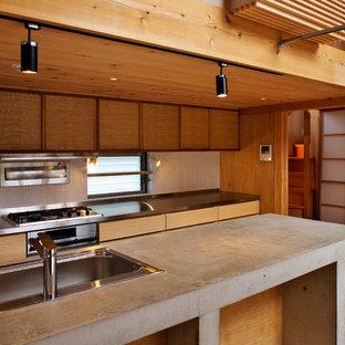 横浜のアジアンスタイルのおしゃれなアイランドキッチン (シングルシンク、フラットパネル扉のキャビネット、中間色木目調キャビネット、コンクリートカウンター、白いキッチンパネル、淡色無垢フローリング、茶色い床) の写真