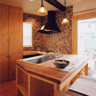 他の地域の地中海スタイルのおしゃれなキッチン (ダブルシンク、中間色木目調キャビネット、木材カウンター、テラコッタタイルの床、オレンジの床、茶色いキッチンカウンター) の写真