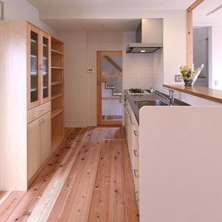 東京都下の北欧スタイルのおしゃれなキッチン (ステンレスカウンター、淡色無垢フローリング、一体型シンク、フラットパネル扉のキャビネット、淡色木目調キャビネット、茶色い床、茶色いキッチンカウンター) の写真