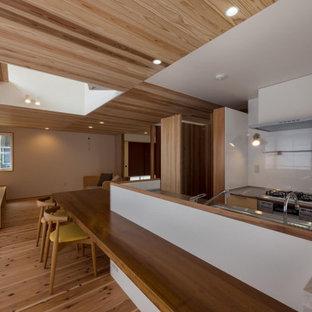 東京都下の広いアジアンスタイルのおしゃれなキッチン (中間色木目調キャビネット、ステンレスカウンター、茶色いキッチンパネル、木材のキッチンパネル、無垢フローリング、ベージュの床、茶色いキッチンカウンター) の写真