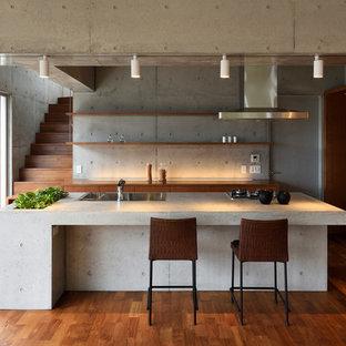 他の地域のモダンスタイルのおしゃれなキッチン (シングルシンク、フラットパネル扉のキャビネット、中間色木目調キャビネット、コンクリートカウンター、無垢フローリング、茶色い床) の写真