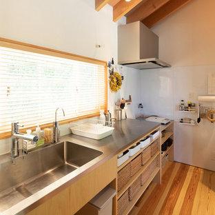 Mittelgroße, Einzeilige Nordische Küche mit integriertem Waschbecken, offenen Schränken, hellbraunen Holzschränken, Edelstahl-Arbeitsplatte, braunem Holzboden, Halbinsel und braunem Boden in Sonstige