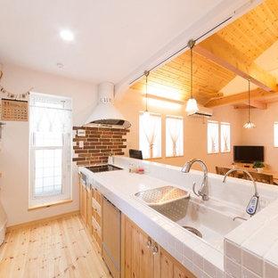 他の地域のアジアンスタイルのおしゃれなキッチン (一体型シンク、中間色木目調キャビネット、タイルカウンター、白いキッチンパネル、淡色無垢フローリング、茶色い床) の写真