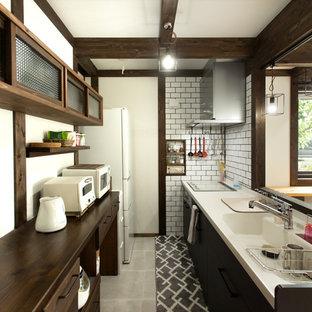 他の地域のコンテンポラリースタイルのおしゃれなキッチン (一体型シンク、フラットパネル扉のキャビネット、黒いキャビネット、白いキッチンパネル、サブウェイタイルのキッチンパネル、白い調理設備、グレーの床、白いキッチンカウンター) の写真